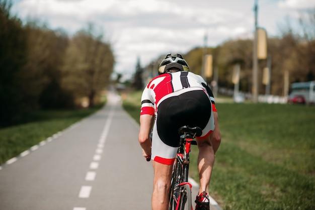 Ciclista anda de bicicleta, vista lateral