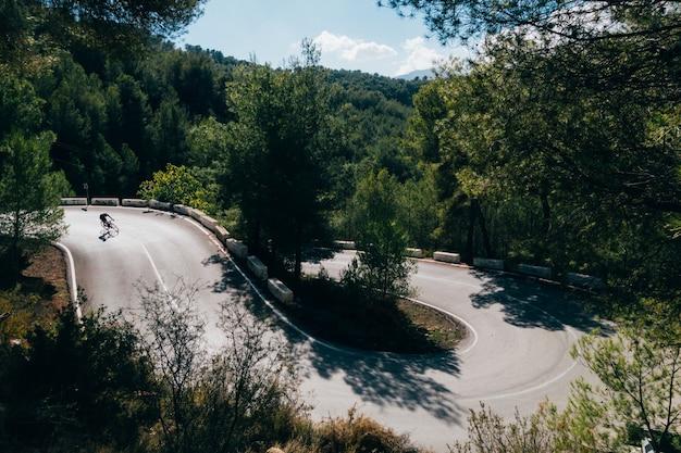 Ciclista andando de bicicleta ao pôr do sol em uma estrada na montanha