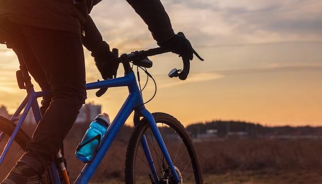 Ciclista andando de bicicleta contra o fundo do céu do sol.