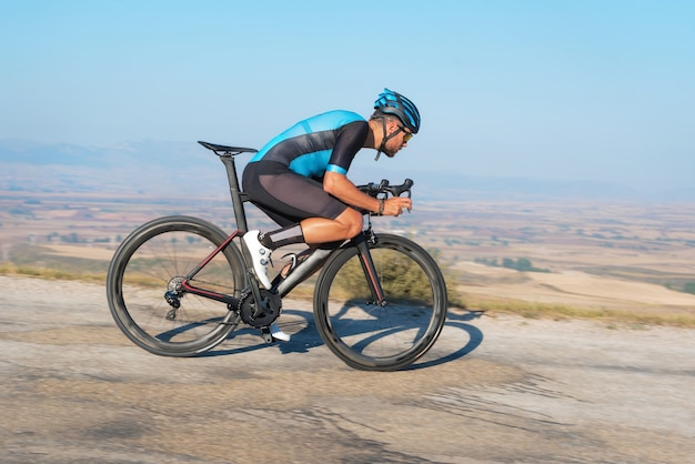 Ciclista andando de bicicleta na estrada descendo a colina