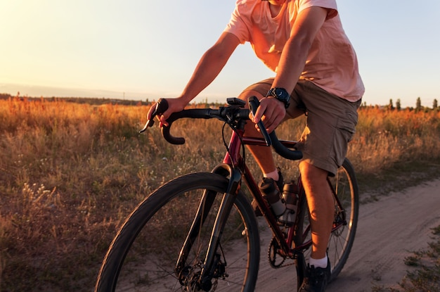 Ciclista andando em um campo ao pôr do sol. homem de bicicleta ao pôr do sol de perto. conceito de estilo de vida ativo.