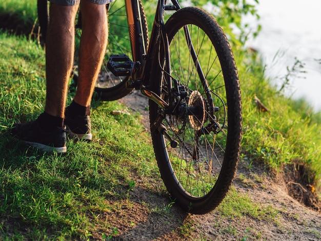 Ciclista ao lado da moto na floresta verde verão ao pôr do sol close-up