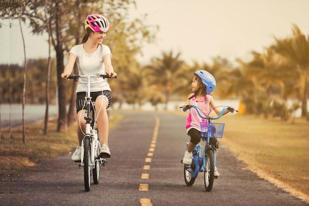 Ciclista asiático da mãe e da filha no parque.