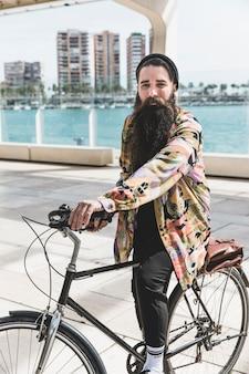 Ciclista ativo andando de bicicleta perto do mar