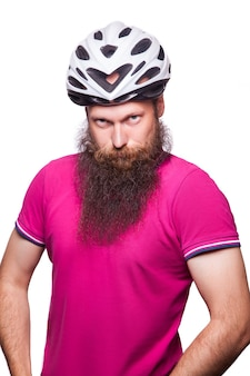 Ciclista barbudo europeu feliz engraçado usando capacete com camiseta rosa ou roxa. aconselhar as pessoas à proteção. tiro do estúdio. isolado no branco.