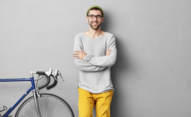 Ciclista barbudo positivo positivo jovem posando na parede em branco cinza com copyspace