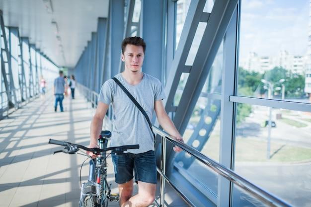 Ciclista bonito parado na ponte.
