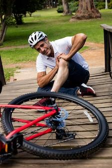 Ciclista caído, segurando o joelho machucado
