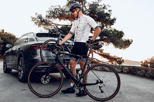 Ciclista carregando sua bicicleta no suporte de seu carro crossover após um passeio
