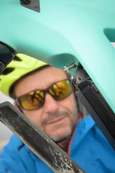 Ciclista coloca a tampa da bateria em sua bicicleta elétrica
