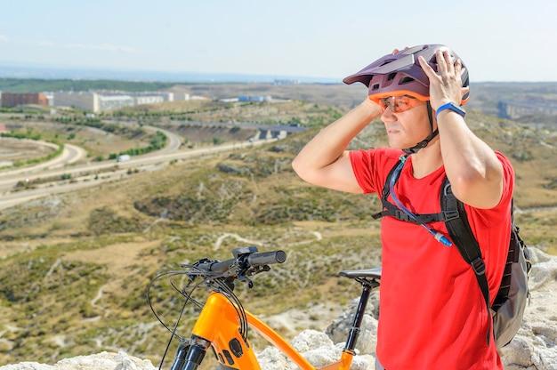 Ciclista colocando capacete na cabeça