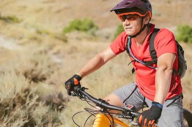 Ciclista com as mãos no guiador voltado para frente