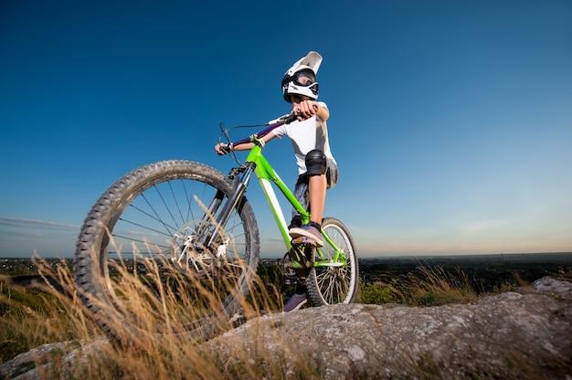 Ciclista com bicicleta de montanha na colina sob o céu azul