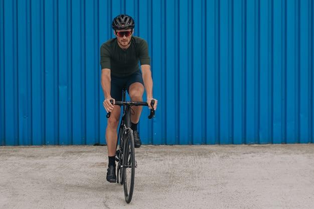 Ciclista com capacete de segurança e óculos andando de bicicleta na rua