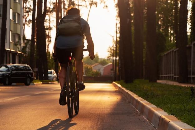 Ciclista com mochila anda de bicicleta de estrada na estrada de asfalto ao pôr do sol.