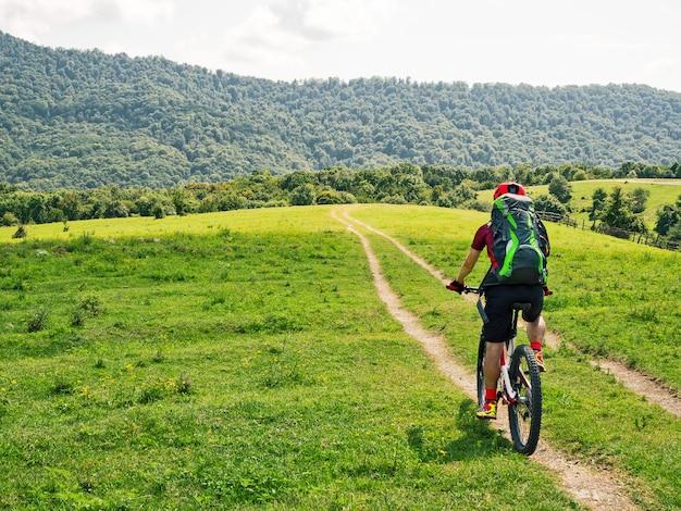 Ciclista com mochila andando de bicicleta de montanha em caminho com fundo de prados verdes