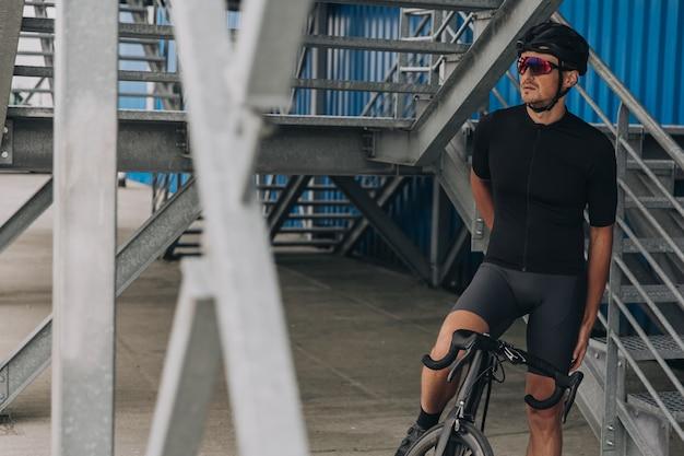 Ciclista com roupas esportivas sentado em uma bicicleta perto da parede azul