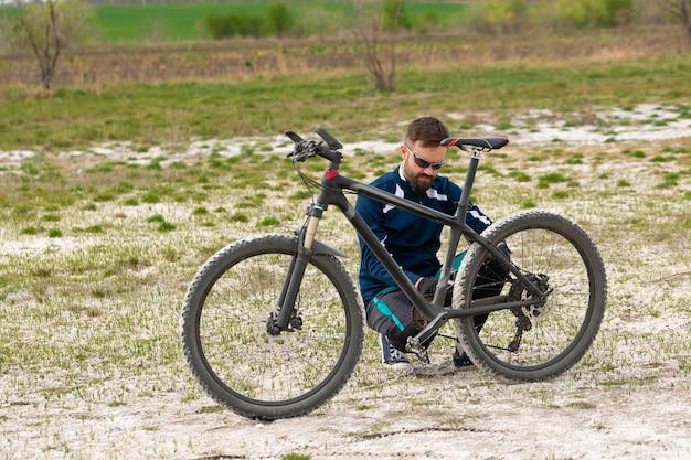 Ciclista conserta sua bicicleta na natureza
