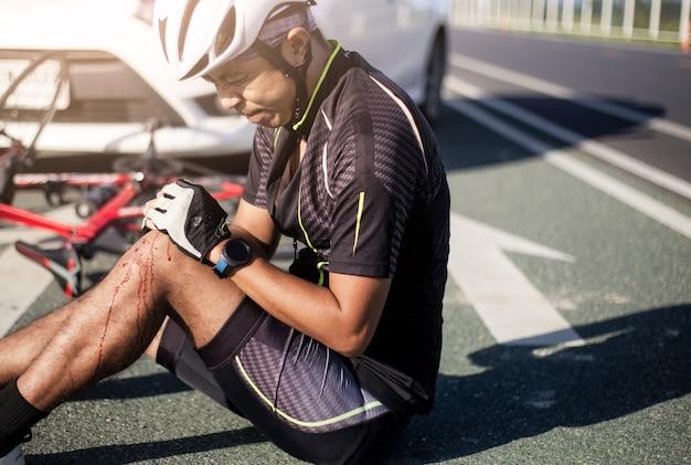 Ciclista de ásia ferido na bicicleta da rua após o carro e a bicicleta do acidente da colisão.