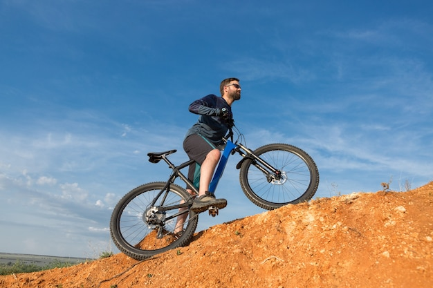 Ciclista de bermuda e malha em uma bicicleta moderna de carbono com suspensão a ar