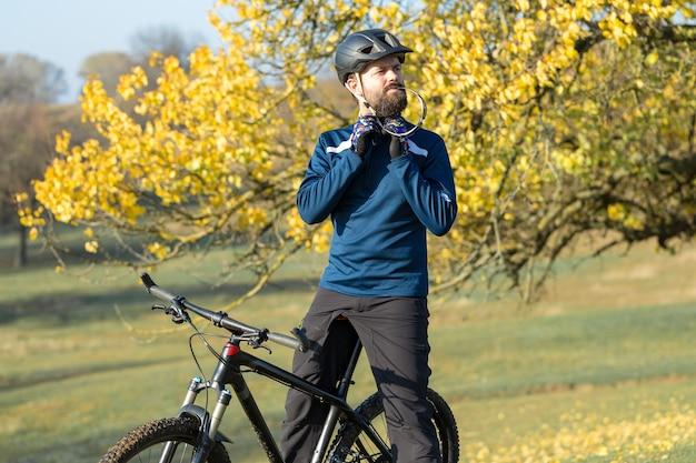 Ciclista de calça e jaqueta de lã em uma bicicleta moderna de carbono com suspensão a ar. o cara no topo da colina anda de bicicleta.