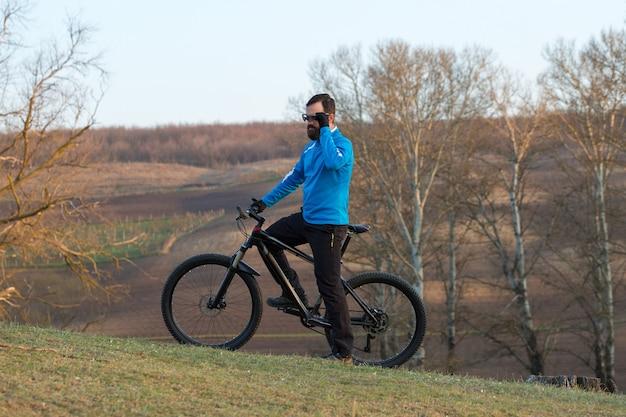 Ciclista de calça e jaqueta de lã em uma bike hardtail moderna de carbono com um garfo com suspensão a ar
