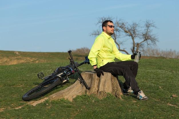 Ciclista de calça e jaqueta verde em uma bicicleta moderna de carbono rígido com um garfo com suspensão a ar