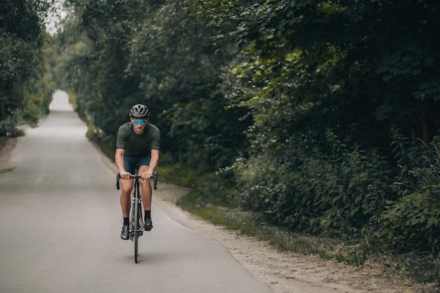 Ciclista de capacete e óculos andando de bicicleta em meio à natureza verde