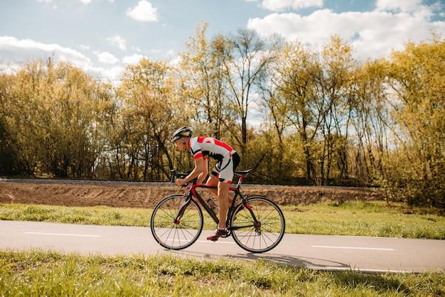 Ciclista de capacete e roupas esportivas anda de bicicleta, vista lateral.