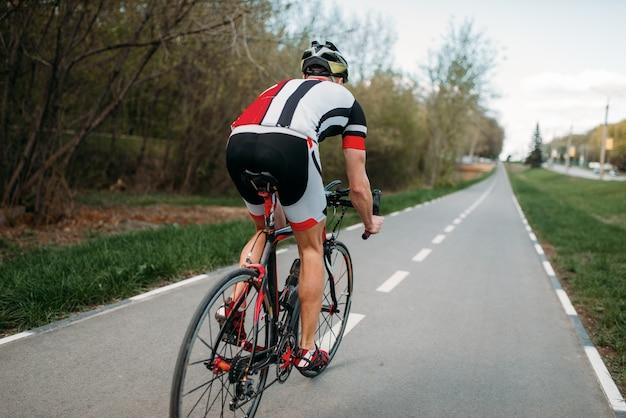 Ciclista de capacete e roupas esportivas anda de bicicleta