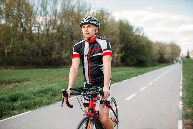 Ciclista de capacete e roupas esportivas em bicicleta esportiva. treino em ciclovia, ciclismo