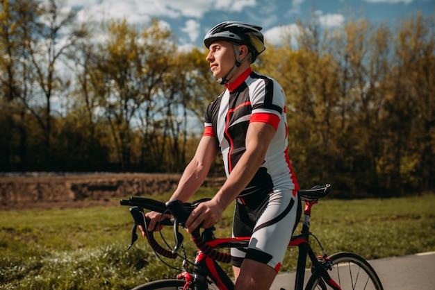 Ciclista de capacete e roupas esportivas na bicicleta esportiva. treino em ciclovia, treino de ciclismo