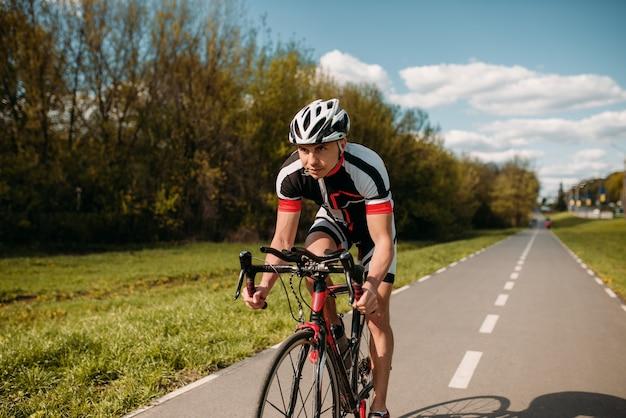Ciclista de capacete e roupas esportivas no treinamento de bicicleta. treino em ciclovia, ciclismo