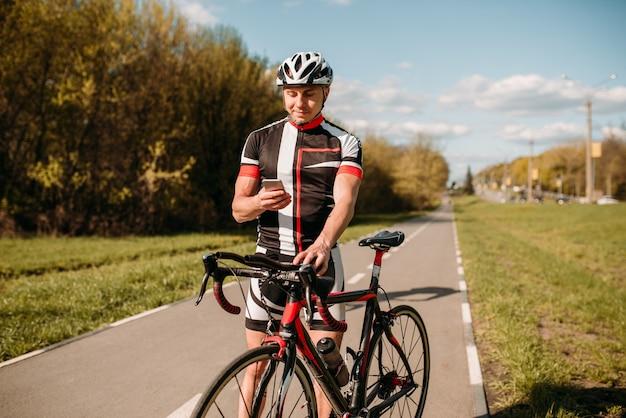 Ciclista de capacete e roupas esportivas, treinando em bicicleta de trilha.