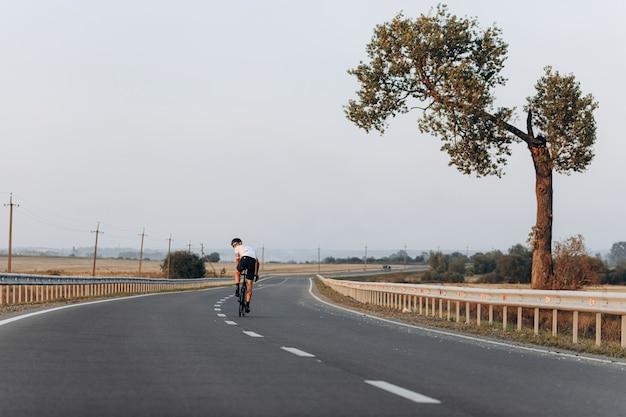 Ciclista de estrada profissional com capacete protetor e roupa esportiva correndo ao ar livre
