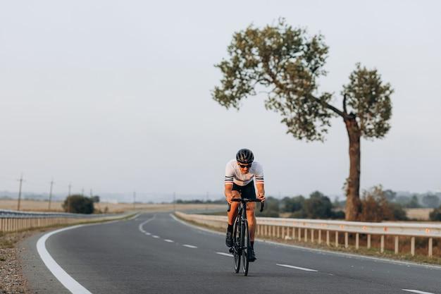 Ciclista de estrada profissional usando capacete de proteção e óculos espelhados em corrida ao ar livre
