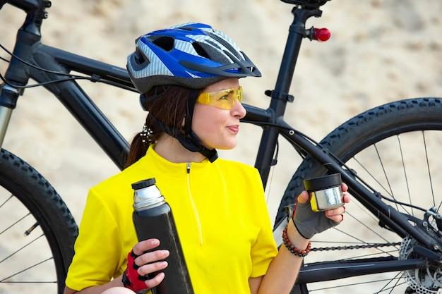 Ciclista de linda garota em amarelo com chá e garrafa térmica na mão na areia. esportes e recreação. natureza e homem
