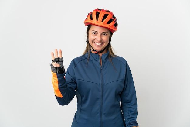 Ciclista de meia-idade isolada no branco feliz e contando três com os dedos