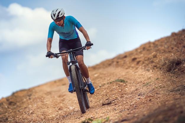 Ciclista de montanha, andar de bicicleta, treinar e subir uma subida íngreme.