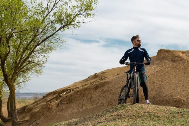 Ciclista de montanha barbada cavalga montanhas e florestas