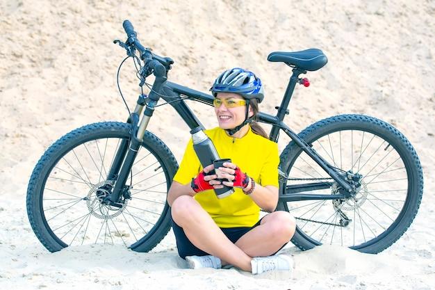 Ciclista de mulher bonita derrama chá de uma garrafa térmica no fundo de uma bicicleta na areia. esportes e recreação. hobbies e saúde.