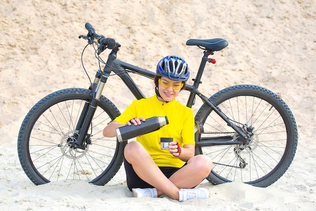 Ciclista de mulher bonita em amarelo com chá e garrafa térmica na mão no espaço de areia. esportes e recreação.
