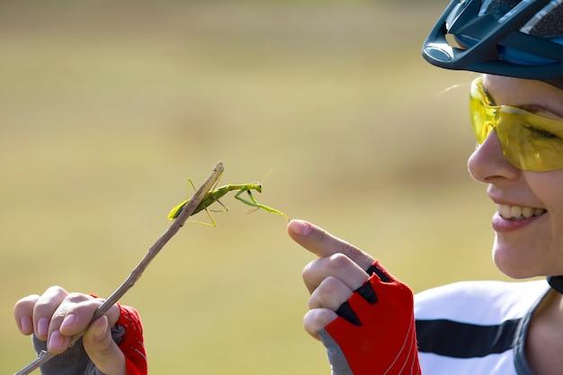 Ciclista de mulher bonita segurando um besouro mantis. natureza e homem