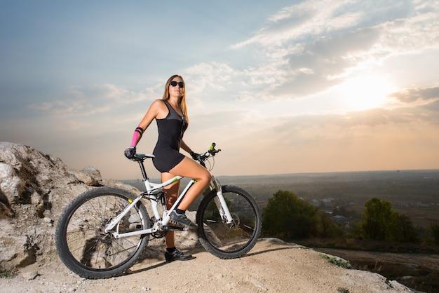 Ciclista de mulher desportivo em uma bicicleta de montanha no penhasco, olhando para a câmera