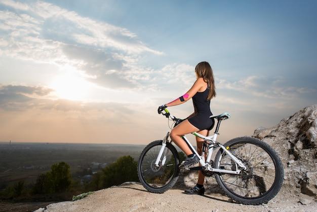 Ciclista de mulher em uma bicicleta de montanha na falésia ao pôr do sol
