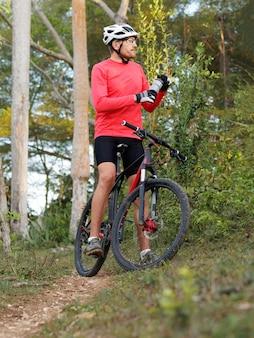 Ciclista descansando e bebendo bebida isotônica na floresta tropical, usa capacete de bicicleta e camisa de ciclismo vermelha.