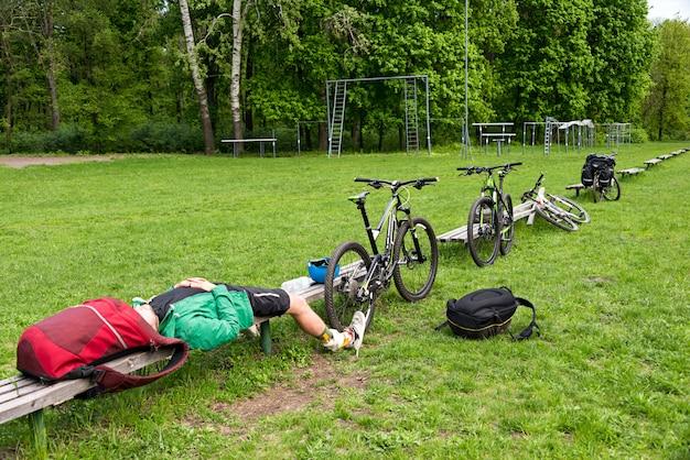 Ciclista descansando em um banco no parque. jovem cansado com sua bicicleta de montanha na floresta descansando e fazendo uma pausa.