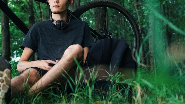 Ciclista descansando sentado no parque junto à árvore. passeio de bicicleta de montanha. ciclista ouvindo música