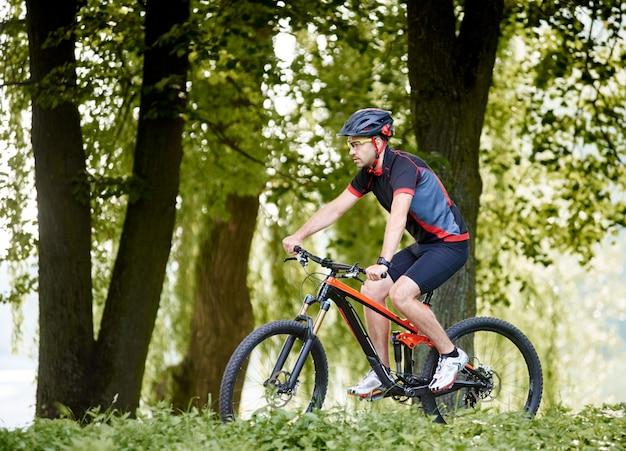 Ciclista desportivo homem andando de bicicleta pelo beco ensolarado entre árvores no parque verde lindo.