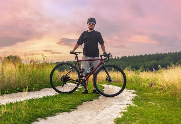 Ciclista em pé com sua bicicleta de cascalho durante o treinamento esportivo ao ar livre ao pôr do sol. estilo de vida ativo.